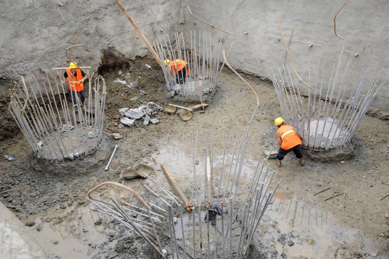 Trabajadores en los casquillos de pila del concreto reforzado foto de archivo