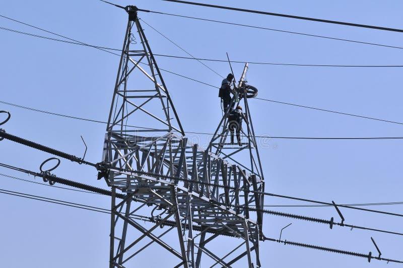 Trabajadores en postes de la electricidad foto de archivo libre de regalías