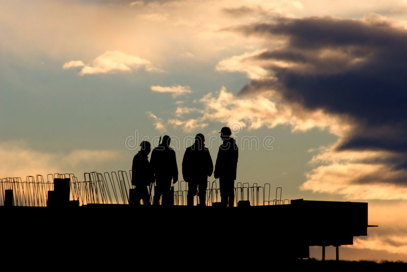 Trabajadores en puesta del sol - silueta foto de archivo