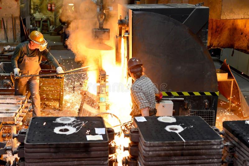 Trabajadores en una fundición que echa un objeto del metal - seguridad en el trabajo y el trabajo en equipo imágenes de archivo libres de regalías