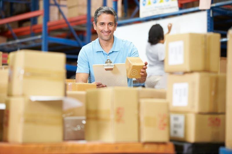 Trabajadores en Warehouse que prepara las mercancías para el envío imágenes de archivo libres de regalías
