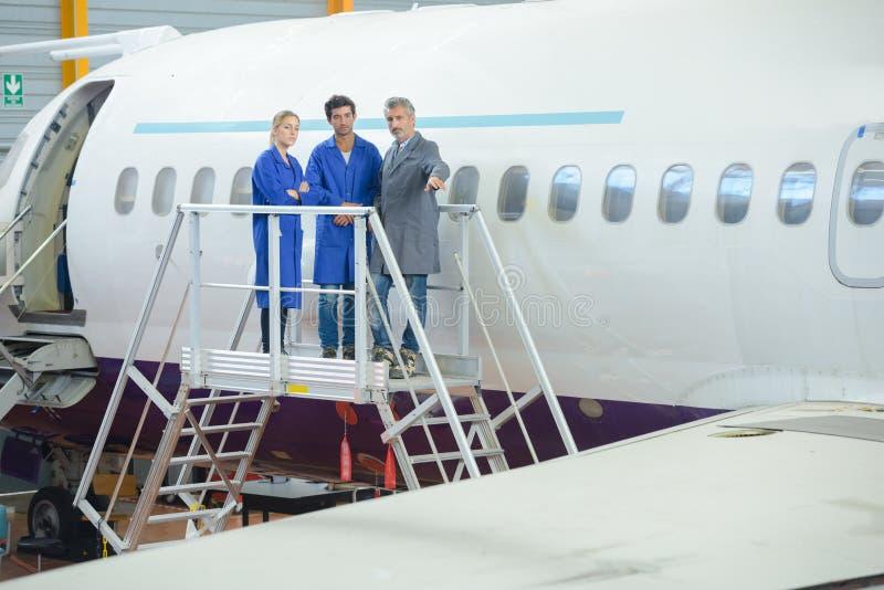 Trabajadores fuera del marco del aeroplano imagenes de archivo