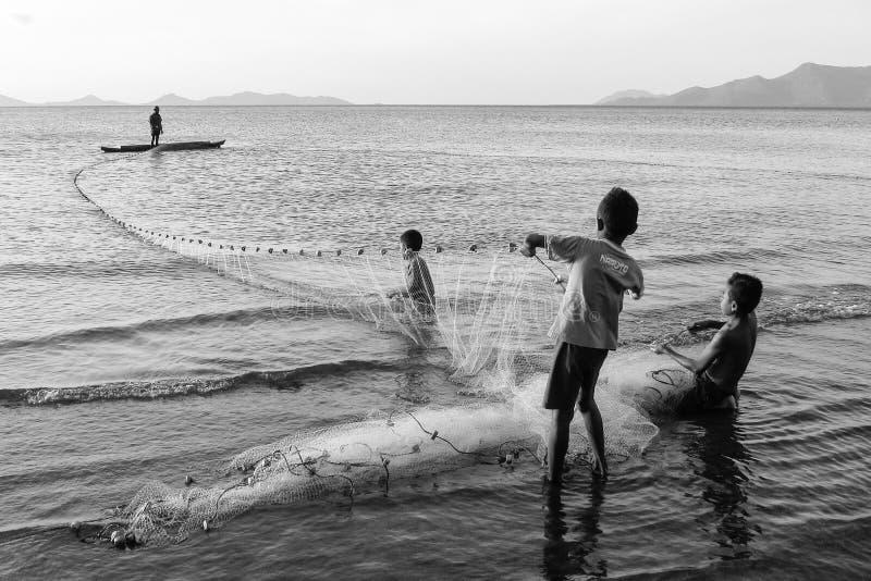 Trabajadores jovenes B/W - con la red de pesca tirando en los días coja, imagen de archivo