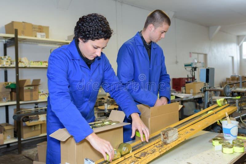 Trabajadores jovenes que embalan productos de cadena de producción de la fábrica imagenes de archivo