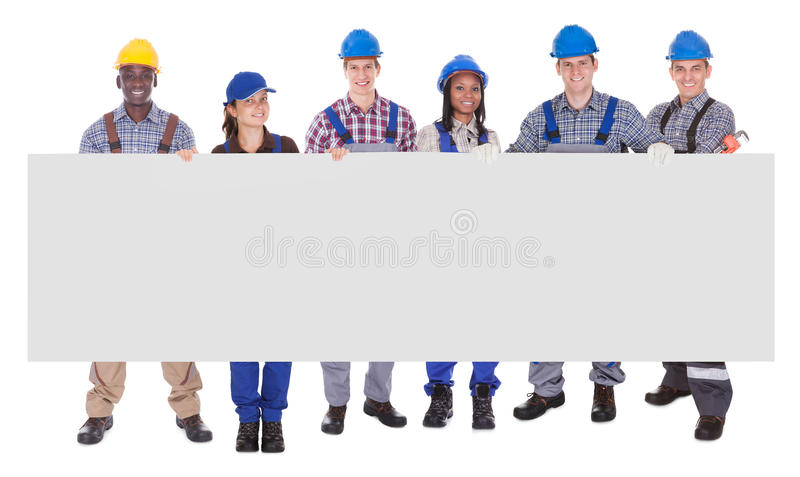 Trabajadores manuales multiétnicos que sostienen la bandera en blanco imagen de archivo