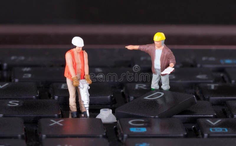 Trabajadores miniatura con el taladro que trabaja en el teclado fotografía de archivo libre de regalías