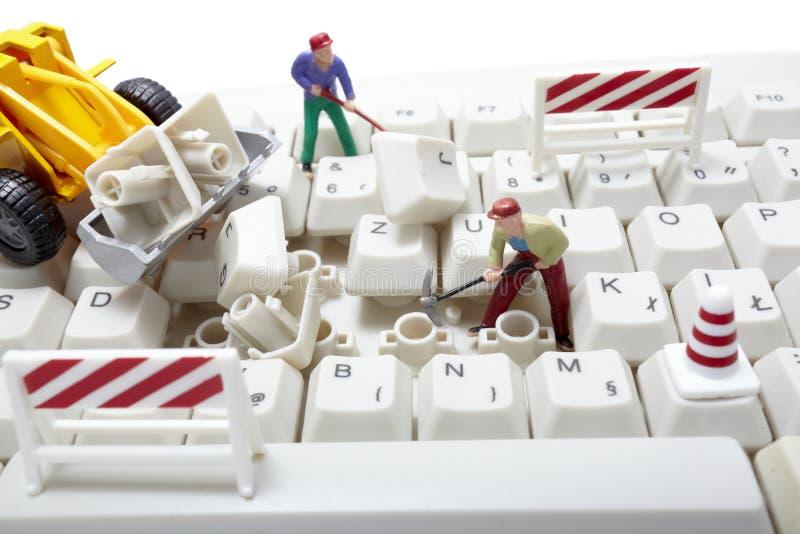 Trabajadores miniatura del juguete que reparan el teclado de ordenador foto de archivo