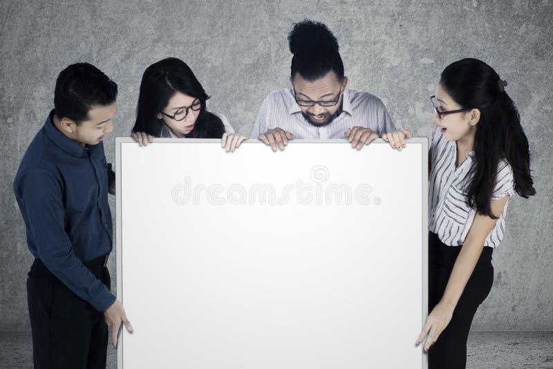 Trabajadores multirraciales que miran whiteboard vacío fotografía de archivo libre de regalías