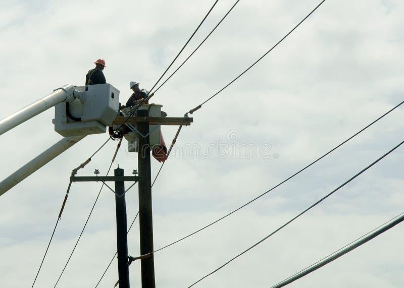 Trabajadores para uso general que reparan los cables de Cherry Picker fotografía de archivo libre de regalías