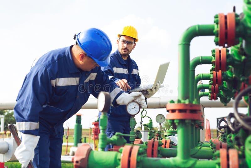 Trabajadores petroquímicos que trabajan en la planta de refinería foto de archivo