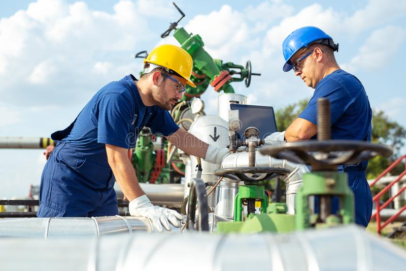 Trabajadores petroquímicos que trabajan en la planta de refinería fotos de archivo libres de regalías