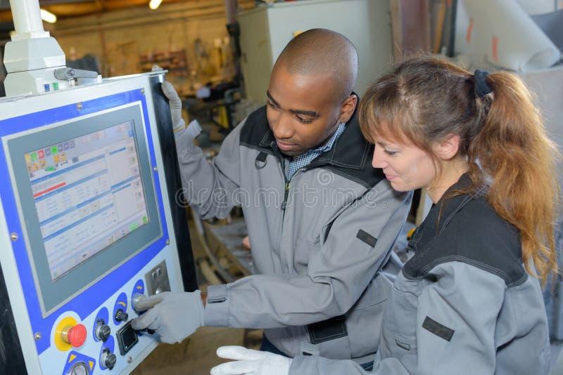 Trabajadores que ajustan controles en el monitor de computadora industrial imágenes de archivo libres de regalías