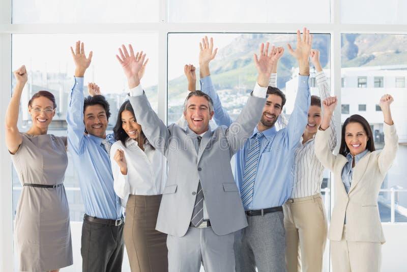 Trabajadores que animan con los brazos aumentados fotografía de archivo