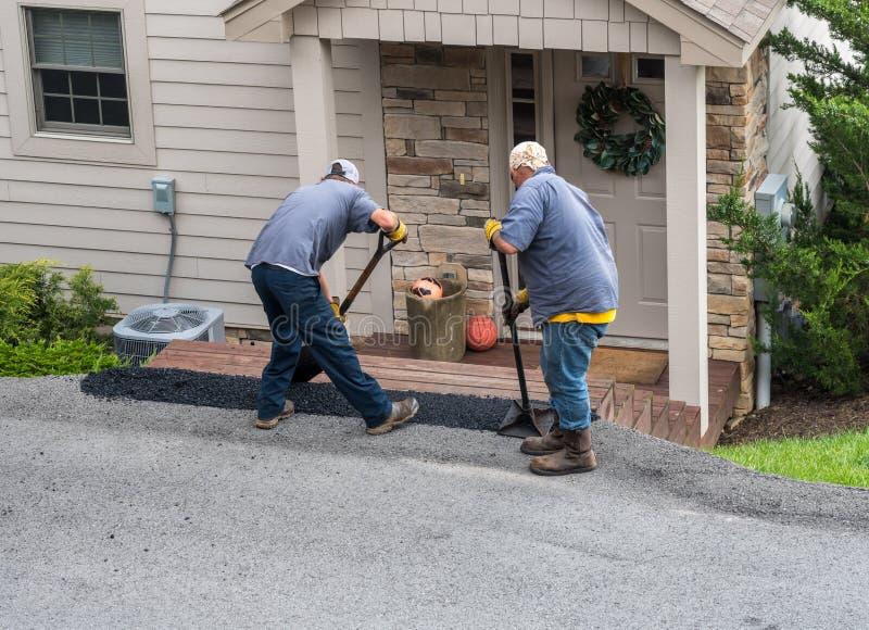 Trabajadores que aplican el blacktop adicional sobre la calle del asfalto imágenes de archivo libres de regalías