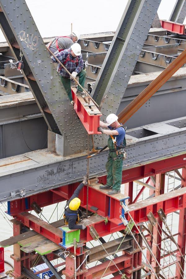 Trabajadores que atan la plataforma que lleva al puente, editorial imagen de archivo