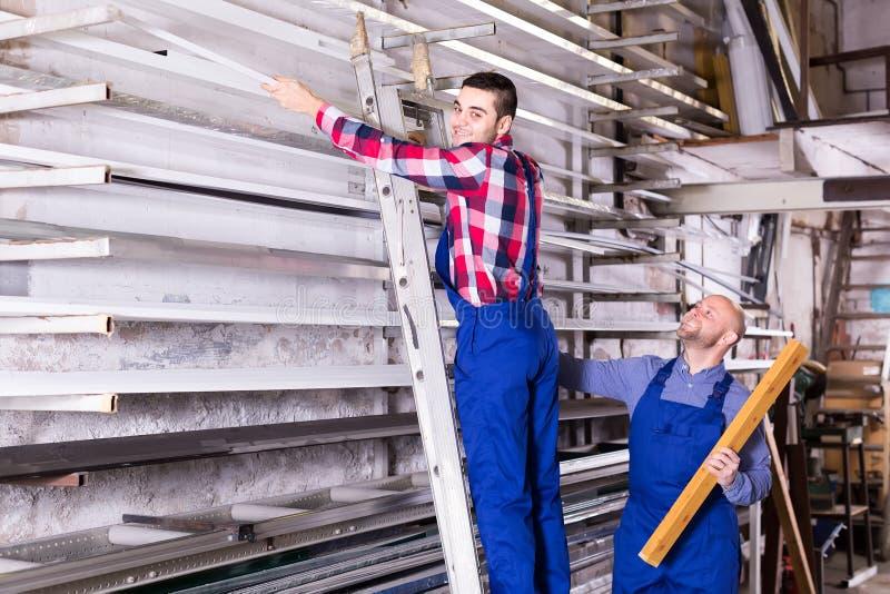 Trabajadores que buscan para los perfiles del PVC fotografía de archivo