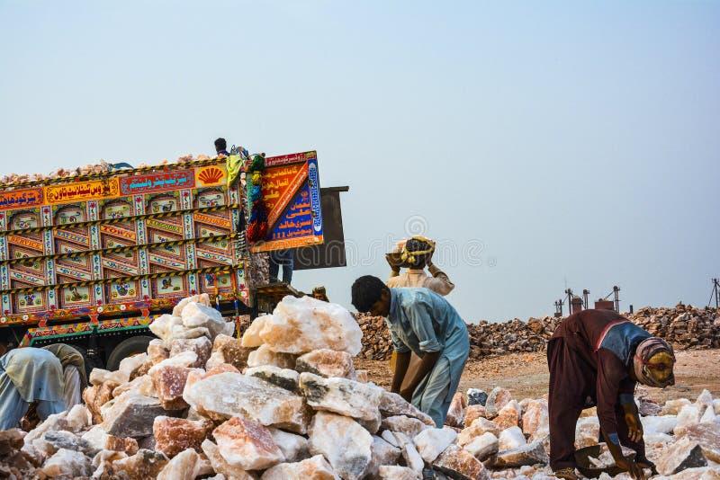 Trabajadores que cargan pedazos de la sal de roca en un camión imagen de archivo