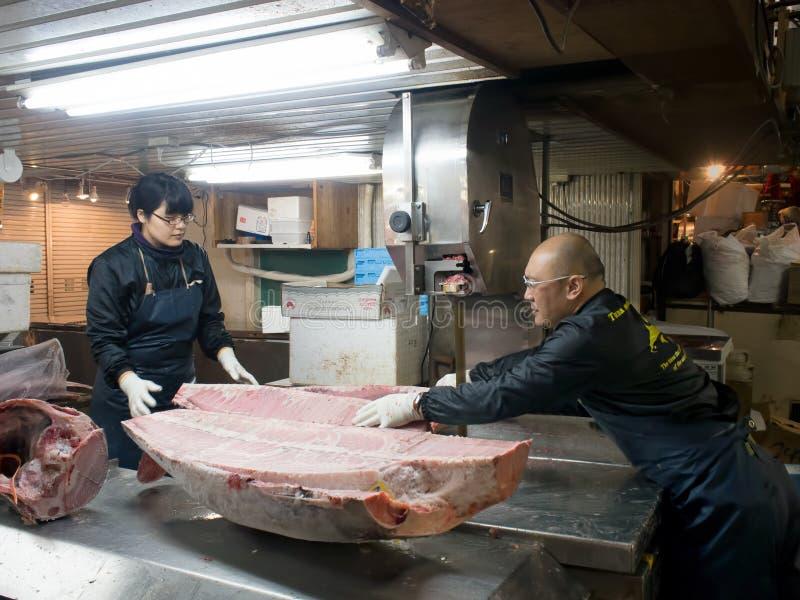 Trabajadores que cortan un atún gigante con la sierra eléctrica fotos de archivo libres de regalías