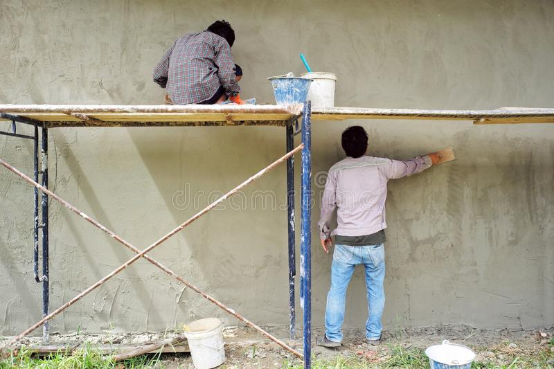 Trabajadores que enyesan la textura del cemento en la pared del ladrillo en el emplazamiento de la obra foto de archivo libre de regalías