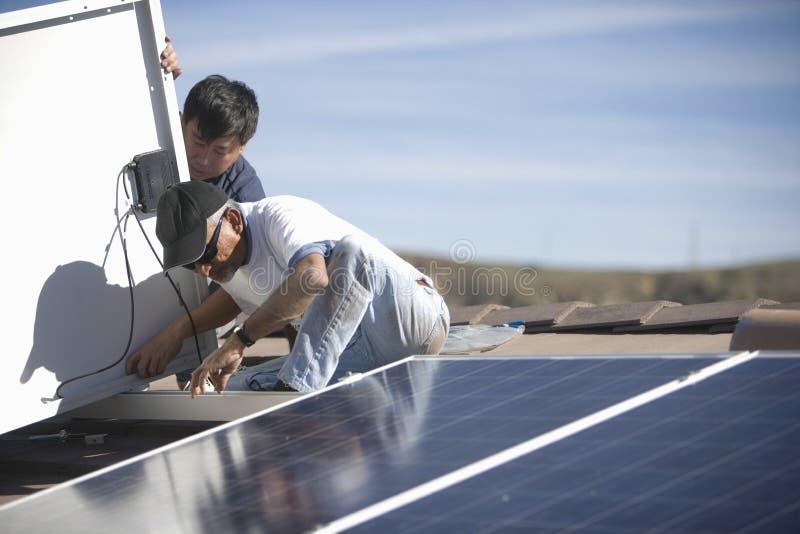 Trabajadores que fijan el panel solar en el top del tejado imagenes de archivo