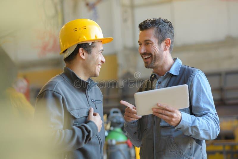 Trabajadores que hablan y que se ríen de la fábrica fotografía de archivo