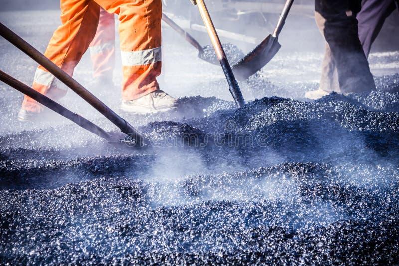 Trabajadores que hacen el asfalto con las palas fotos de archivo libres de regalías