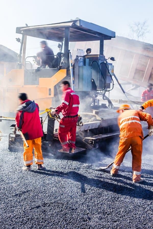 Trabajadores que hacen el asfalto con las palas en el camino fotografía de archivo libre de regalías