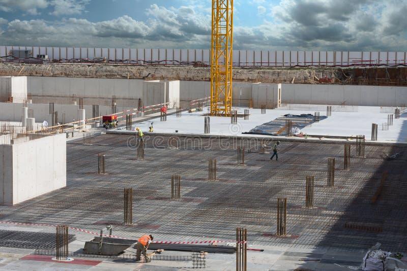 Trabajadores que hacen el marco para el piso concreto imagen de archivo