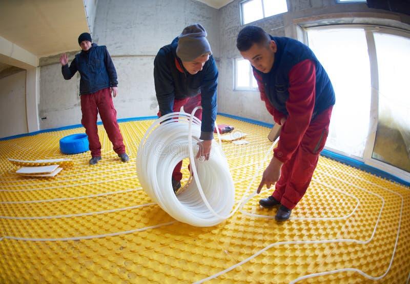 Trabajadores que instalan el sistema de la calefacción por el suelo imagen de archivo