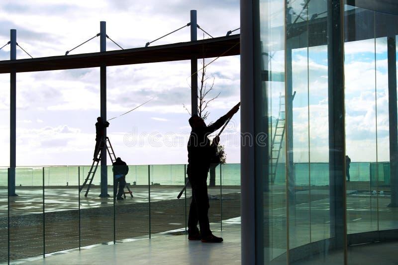 trabajadores que limpian el punto de vista de cristal de las construcciones imagenes de archivo