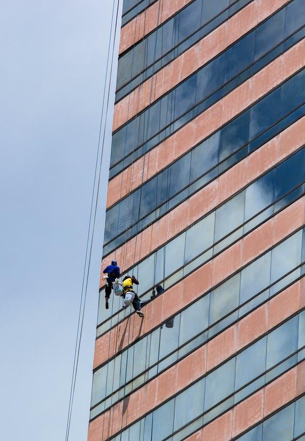 Trabajadores que limpian servicio de las ventanas imagenes de archivo