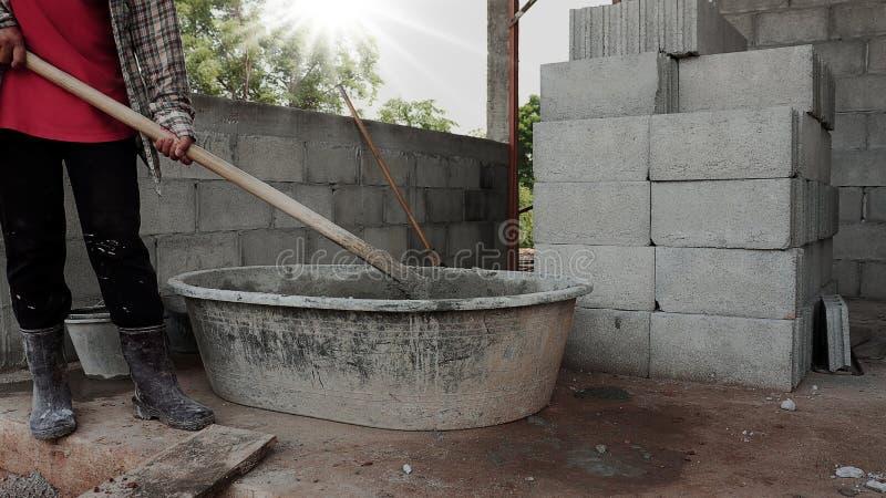 Trabajadores que mezclan cemento para la construcción foto de archivo