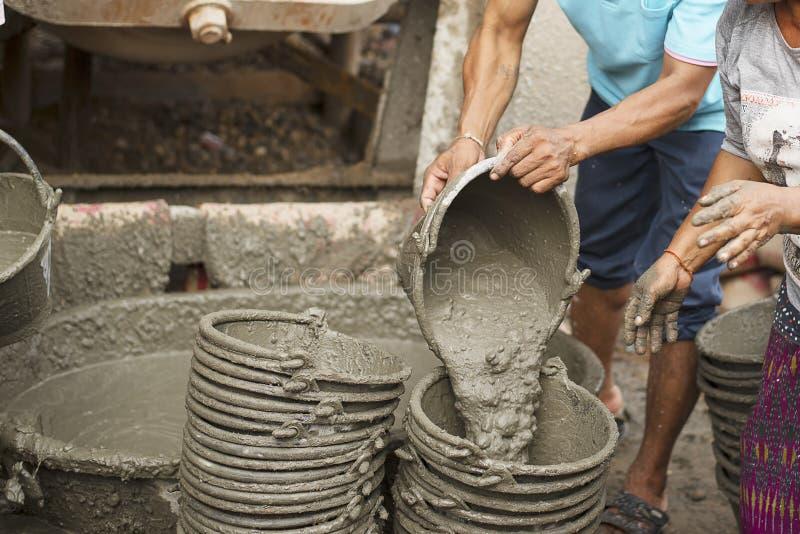 Trabajadores que mezclan el cemento foto de archivo