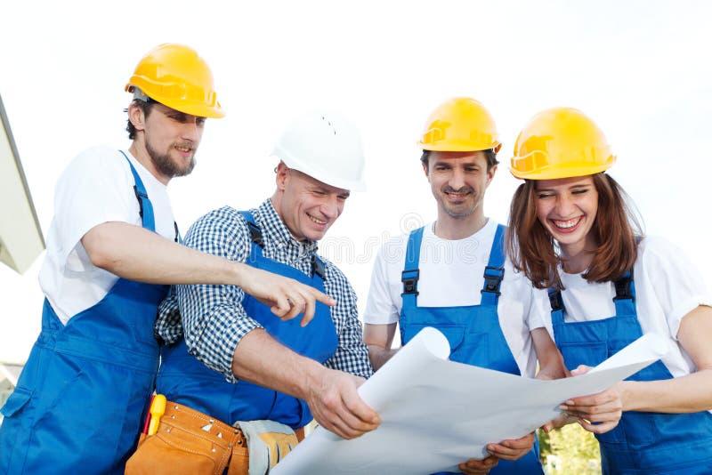 Trabajadores que miran diseño de la casa imagen de archivo