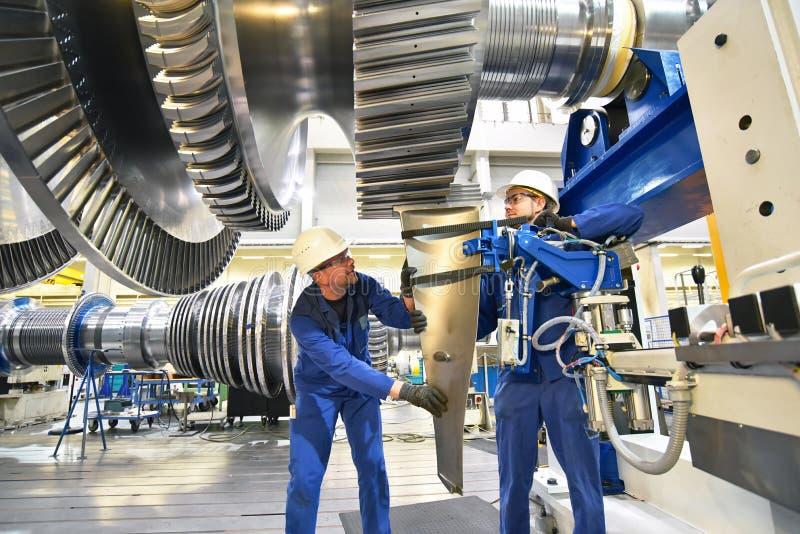 Trabajadores que montan y que construyen las turbinas de gas en un ind moderno fotografía de archivo