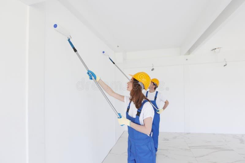 Trabajadores que pintan la pared fotos de archivo