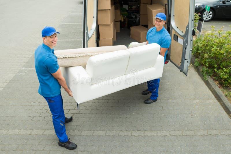 Trabajadores que ponen los muebles y las cajas en el camión foto de archivo libre de regalías