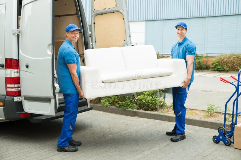 Trabajadores que ponen los muebles y las cajas en el camión imagenes de archivo