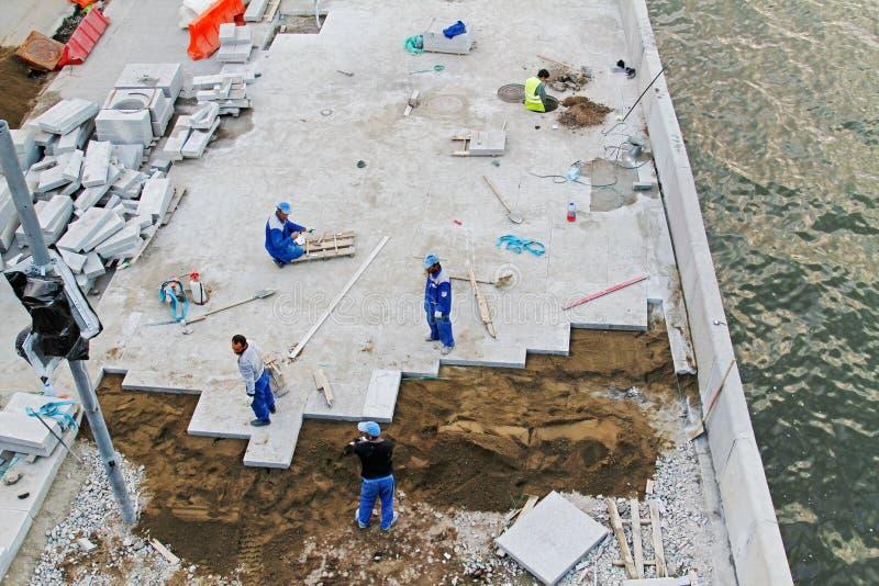 Trabajadores que ponen pavimentando las tejas del camino en la costa en Moscú fotografía de archivo