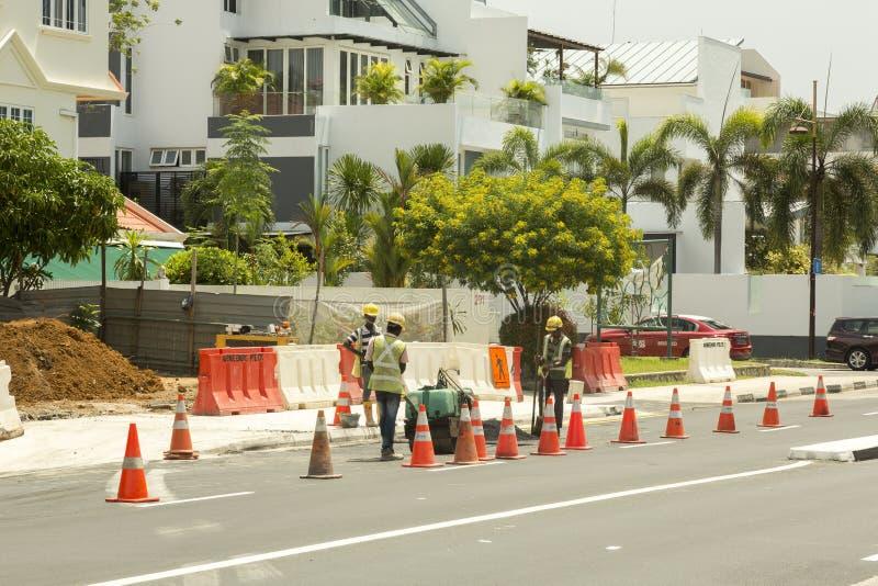 Trabajadores que reparan el camino en Singapur imagenes de archivo
