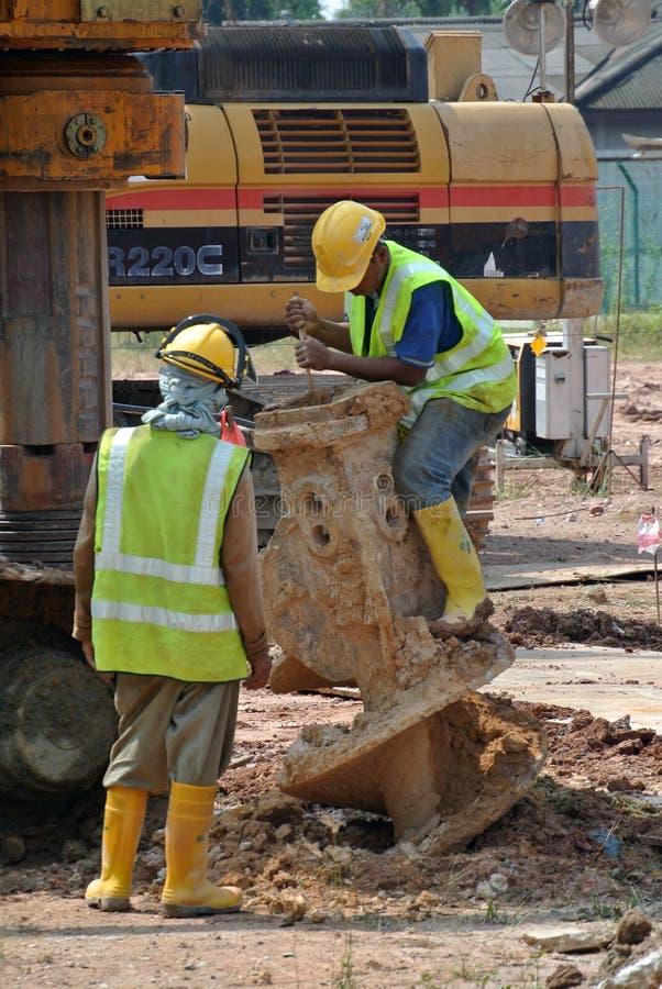 Trabajadores que reparan el taladro del aparejo de la pila del diámetro interior en el emplazamiento de la obra foto de archivo libre de regalías