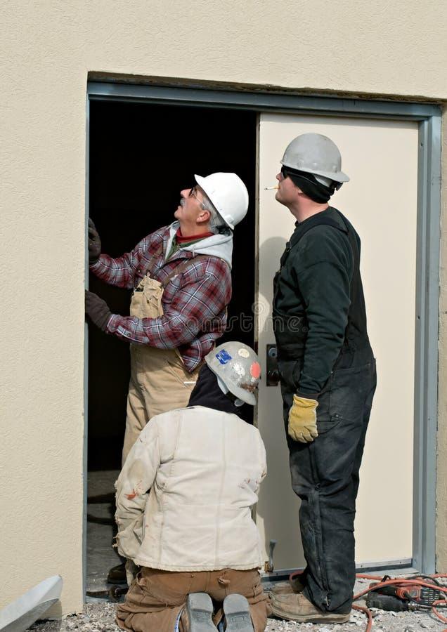 Trabajadores que reparan la puerta imagen de archivo libre de regalías