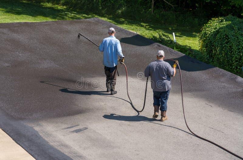 Trabajadores que rocían el sellador del blacktop o del asfalto sobre el camino imágenes de archivo libres de regalías