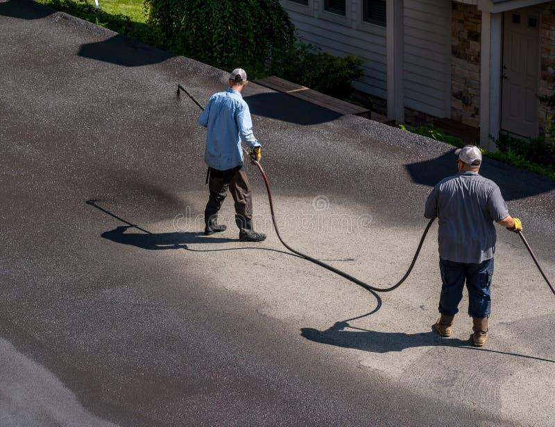 Trabajadores que rocían el sellador del blacktop o del asfalto sobre el camino foto de archivo