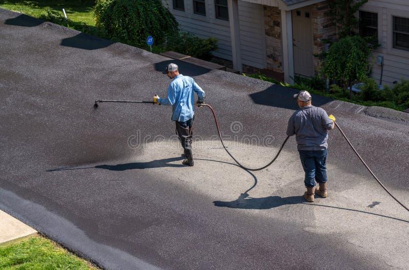 Trabajadores que rocían el sellador del blacktop o del asfalto sobre el camino foto de archivo libre de regalías