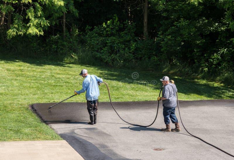 Trabajadores que rocían el sellador del blacktop o del asfalto sobre el camino imagen de archivo libre de regalías