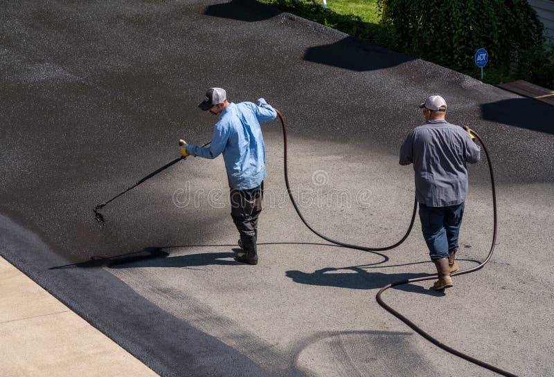 Trabajadores que rocían el sellador del blacktop o del asfalto sobre el camino fotografía de archivo