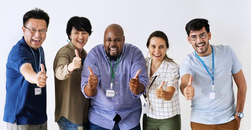 Trabajadores que se levantan y que muestran sus pulgares junto foto de archivo libre de regalías