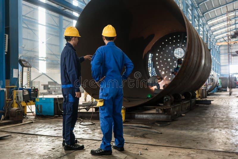 Trabajadores que supervisan la fabricación de un cilindro metálico imagenes de archivo