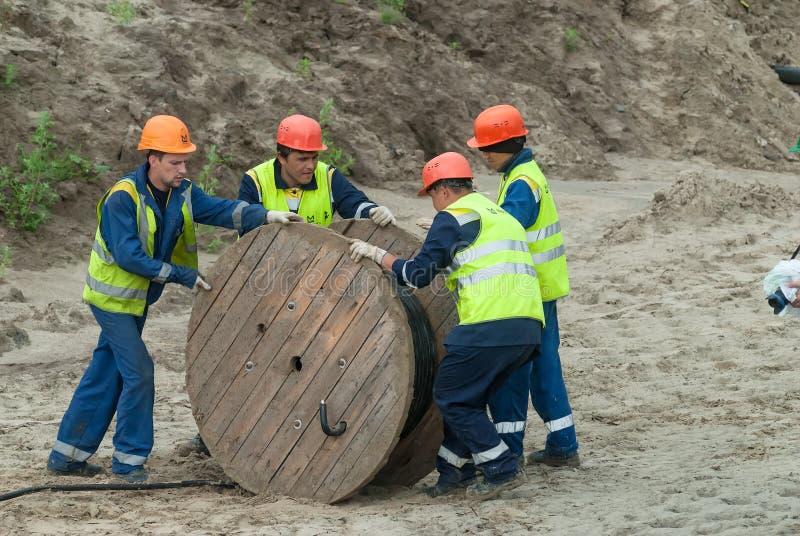 Trabajadores que tiran de la línea del cable de tensión del rollo fotos de archivo libres de regalías